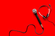 Leinwanddruck Bild - Television concept. Microphone and headset on red background top-down copy space