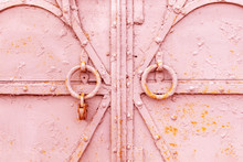 Closeup Fragment Of A Closed Old Metal Door Or Gate With Round Knockers And A Rusty Padlock. Shabby Worn Texture Of Iron With Pieces Of Peeling Pink Paint Layer And Spots Of Red Rust, Background.