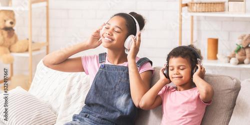 African sisters enjoying favorite music in headphones Wallpaper Mural