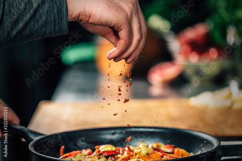 Fototapeta Sprinkling Ground Red Chili Pepper Paprika over Sliced Vegetables obraz
