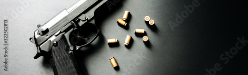 Foto Gun with bullets lying on the table