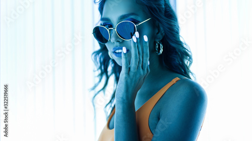 Obraz Pretty beautiful sensual young hipster woman in sunglasses in a stylish swimsuit with trendy manicure enjoys ultraviolet rays in a solarium. Portrait of a sexy girl with tanned skin in a tanning bed. - fototapety do salonu