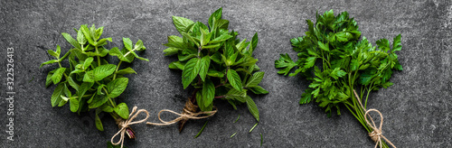 Obraz Fresh herbs background, bunches of freshly harvested green herbs from the garden on dark background - fototapety do salonu