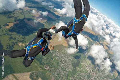 Fotografie, Obraz Two skydivers free falling over the clouds