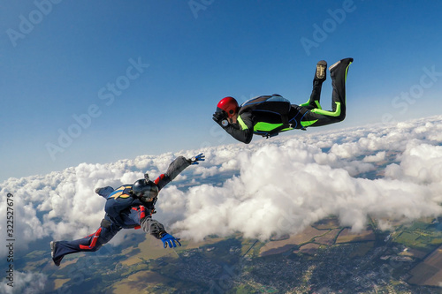 Fototapeta Two skydivers over the clouds during freefall