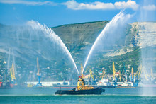 Floating Tug Boat Is Spraying Jets Of Water, Demonstrating Firefighting Water Cannons