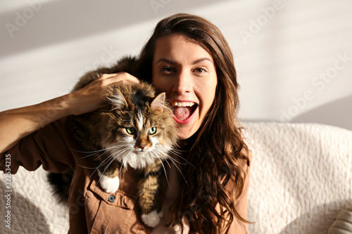 Portrait of young woman holding cute siberian cat with green eyes Wallpaper Mural