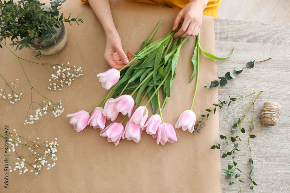 Fototapeta Unrecognizable young woman wearing mustard yellow shirt making a beautiful bouquet of flowers. Female florist at work concept. Close up, copy space, background.