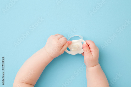 Infant hands holding white soother on light blue floor background Fototapet