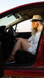 Beautiful sexy blonde woman, red car, field