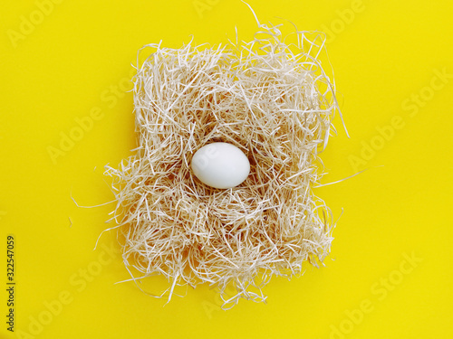 Stampa su Tela A white chicken eggs are placed in the hay lay flat on yellow background, close up in the center with copy space