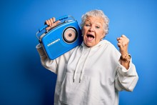 Senior Beautiful Woman Holding Vintage Radio Standing Over Isolated Blue Background Screaming Proud And Celebrating Victory And Success Very Excited, Cheering Emotion