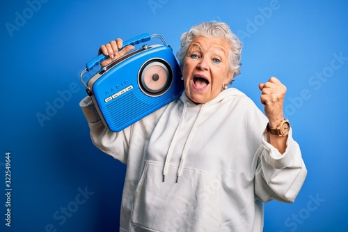 Senior beautiful woman holding vintage radio standing over isolated blue backgro Fototapet