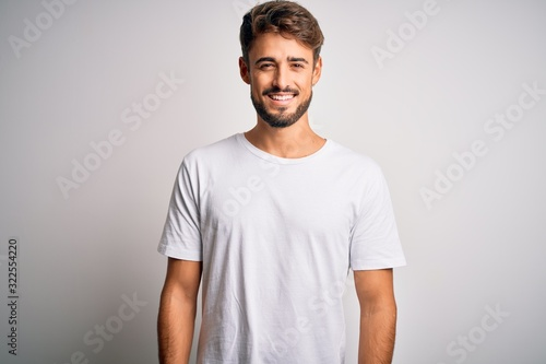 Canvas Print Young handsome man with beard wearing casual t-shirt standing over white background with a happy and cool smile on face