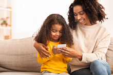 Afro Mother And Daughter Using...