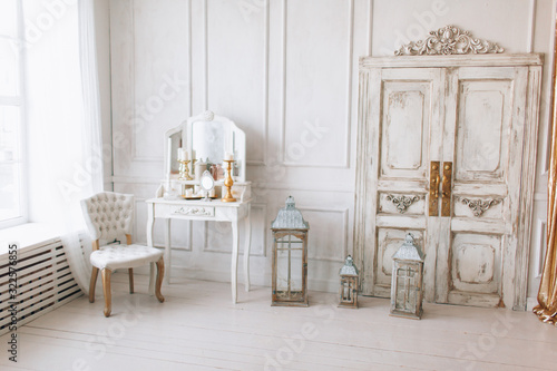 Obraz beautiful  light interior. classic room with wooden floor white walls with moldings, dressing  table with mirror decorated with elements, chair, sofa, lanterns, gold curtains vintage old door - fototapety do salonu
