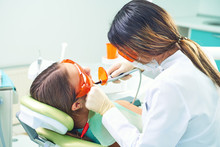Girl Child At The Doctor. Dentist Places A Filling On A Tooth With Dental Polymerization Lamp In Oral Cavity. Over Clinic Background