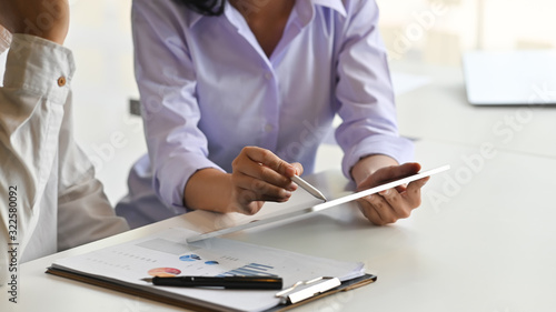 Cropped shot of young project administrator explaining information to her customer by using stylus pen and tablet at the modern working desk with comfortable meeting room as background Canvas Print
