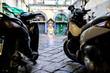 zwei Mofas Motorroller stehen auf einem gepflastertem Innenhof mit einer religiösen Gedenkstätte in der Mitte