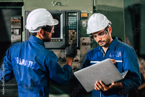 Fototapeta industry engineer team worker operate control heavy machine with computer laptop to help analysis operating problem. obraz