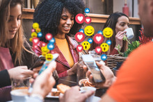 Social Network Emoticons That Pops Up Over The Smartphones Of A Young Group Of People Sitting At A Coffee Table Having Breakfast Together. People Using Social Media Application Concept.