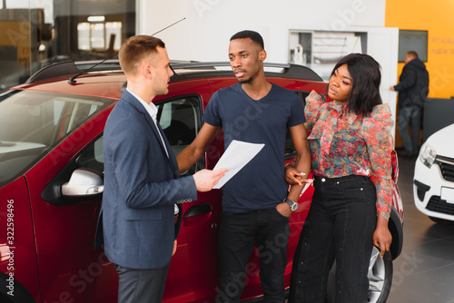 Fototapety, obrazy: happy woman receiving a new car from her husband at dealership
