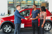 Young African Couple Buying New Car At Dealership