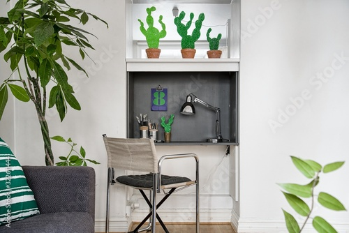 Fotografering Study area with a lamp, penholders and a calendar with cactus plants on the top