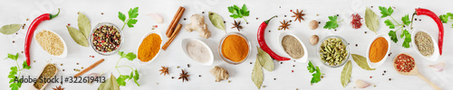 Various assorted colorful spices and herbs on white wooden background top view. Banner size.