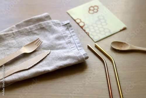 Linen cloth, reusable straws, wooden cutlery and beeswax wrap on a wooden table Wallpaper Mural
