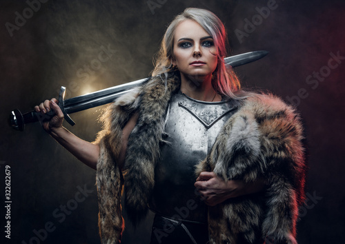 Fotografiet Portrait of a beautiful warrior woman holding a sword wearing steel cuirass and fur