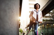 canvas print picture - Happy beautiful female riding an electric scooter on the street