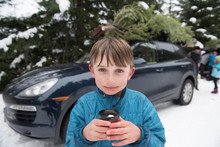 A Boy Holds A Cup Of Hot Chocolate After Cutting A Christmas Tree.