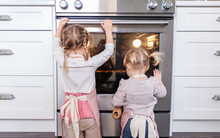 Toddlers Looking Into Oven At ...