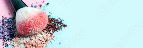 Obraz Beautiful bright makeup brush on a trendy pastel pink and blue background. Beauty banner. Cosmetic products. Crumbled multicolored eyeshadow. Place for text and design. Copy space. - fototapety do salonu