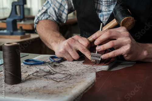 Fotografia Close up of leather craftsman hands working with natural leather using hammer