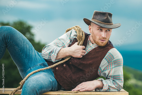 Sexy masculine stylish cowboy macho man holding lasso rope. Western style men fashion. Handsome cowboy in plaid shirt at beautiful rural nature background.