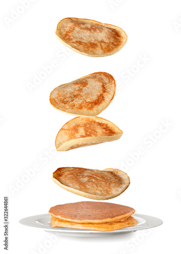 Plate with falling pancakes on white background Wall mural