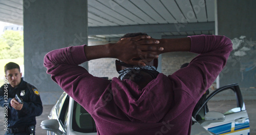 Close-up black man perpetrator wearing mask raising his hands by police order Canvas Print