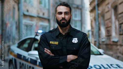 Fotografia Close up serious young man cops hold pistol stand near patrol car look at camera