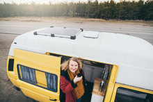 Young Blond Woman Looking Out Of Camper Van With Solar Panel On The Roof Top And Pine Forest On The Background