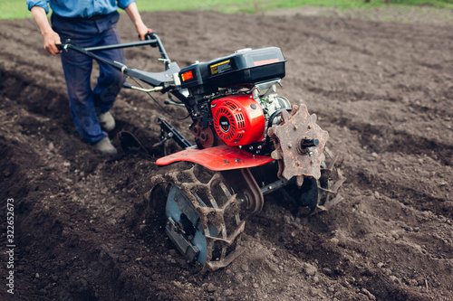 Farmer man driving small tractor for soil cultivation and potato planting. Spring agriculture preparation