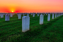 National Cemetery With Rows Of White Gravestones. The Sunset Sun Above The Ocean In San Diego Bay At Point Loma, California, United States.