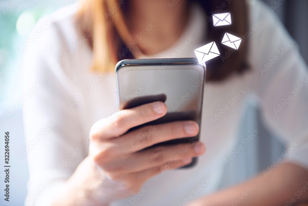 Fototapeta Email concept, Closeup Woman hand using mobile smartphone with email icon.