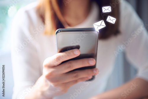Fotomural Email concept, Closeup Woman hand using mobile smartphone with email icon
