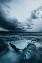Russia. Lake Baikal. March. Cracked Ice. Blocks Of Ice. Dark Cloudy Stormy Sky. Blue Photo
