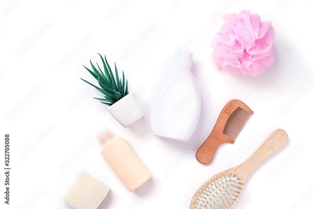 Fototapeta White shampoo bottle, hair balm, natural soap, wooden comb, aloe vera and pink sponge. Organic spa cosmetic flat lay photo