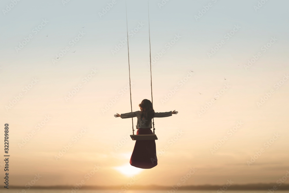 Fototapeta special contact between nature and a woman with open arms on a swing