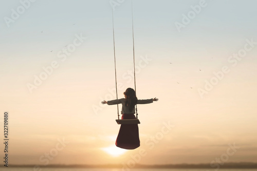 Fotomural special contact between nature and a woman with open arms on a swing