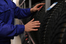 Male Mechanic With Car Tire In Auto Store, Closeup